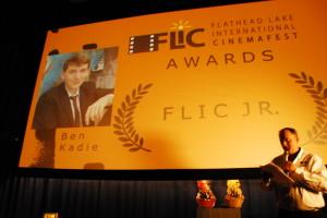 Daniel Smith in front of the movie screen announcement of Ben Kadie as FLIC Jr. winner.