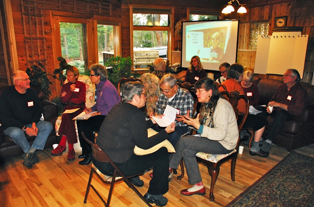 Several groups of three participants sit knee-to-knee during discussions at the Jette Lake neighborhood gathering of Polson Heart & Soul.